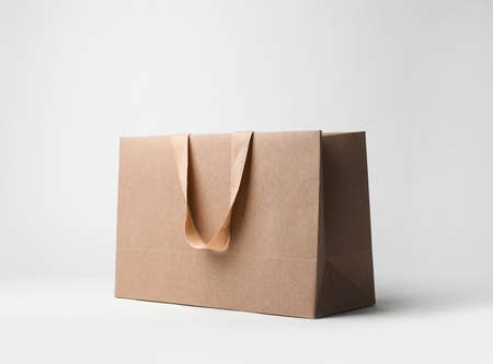 Paper shopping bag with comfortable handles on white background. Mockup for design