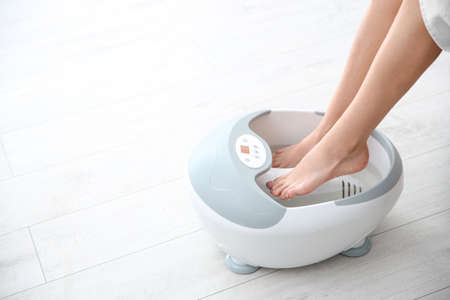 Woman with beautiful legs using foot bath at home, closeup with space for text. Spa treatment Stock Photo