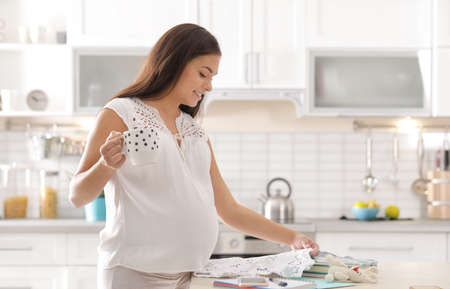 Pregnant woman preparing baby clothes for maternity hospital in kitchen