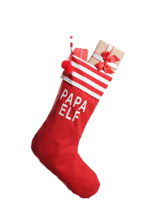 Red Christmas stocking full of gift boxes on white background. Interior decor