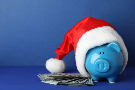 Sparschwein mit Weihnachtsmütze und Dollar-Banknoten auf Farbhintergrund. Platz für Text