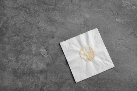 Dirty napkin with coffee stain on grey background, top view. Space for text