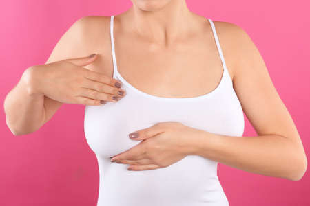 Woman checking her breast on color background, closeup Standard-Bild - 112745314