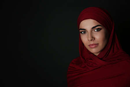 Portrait of Muslim woman in hijab on dark background. Space for text
