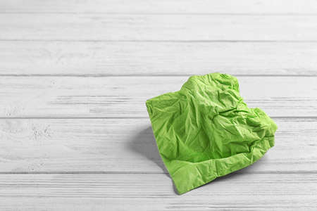 Crumpled napkin on wooden background, space for text. Personal hygiene