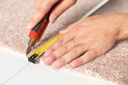 Man cutting new carpet flooring indoors, closeup