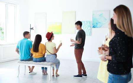 Grupa ludzi z kieliszkami szampana na wystawie w galerii sztuki
