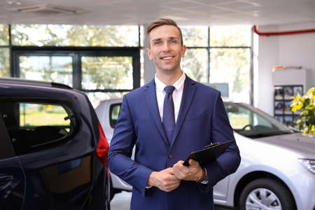 Portrait of young car salesman in dealership Stockfoto