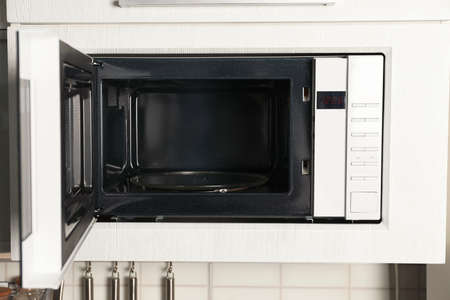 Open modern microwave oven built in kitchen furniture