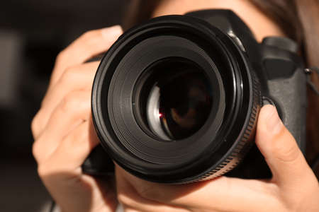 Female photographer with professional camera on blurred background, closeup Stock Photo