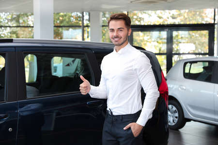 Young man near new car in dealership