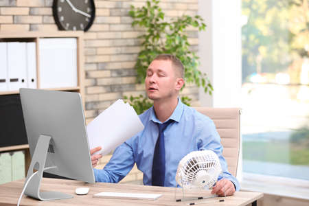 Young man suffering from heat in front of small fan at workplace Stock Photo