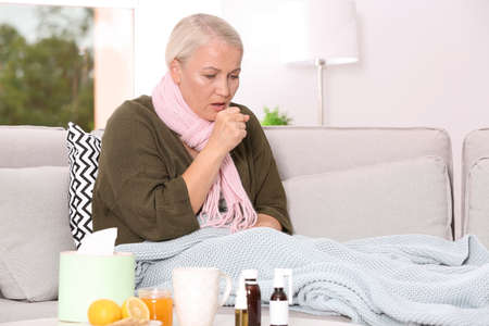 Ill mature woman suffering from cough on sofa