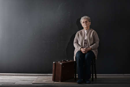 Poor elderly woman sitting on chair near suitcase. Space for text