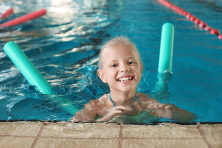Little girl with swimming noodle in indoor pool Archivio Fotografico