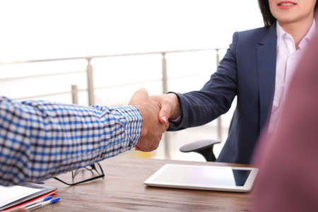 Human resources manager shaking hands with applicant during job interview in office, closeup