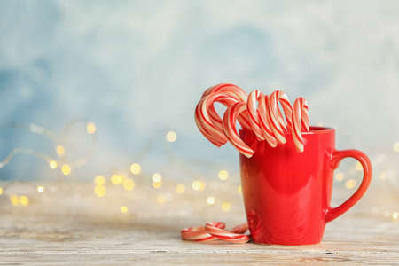Tasty Christmas candy canes in cup on table. Space for text