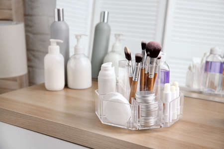 Organizer with cosmetic products on wooden table in bathroom 写真素材