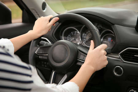 Woman holding steering wheel in car, closeup. Driving license test 版權商用圖片 - 112877266