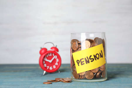 Coins in glass jar with label PENSION on table against light wall. Space for text Stock Photo