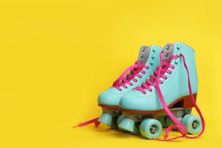 Par de patines de cuatro ruedas con estilo sobre fondo de color. Espacio para texto Foto de archivo