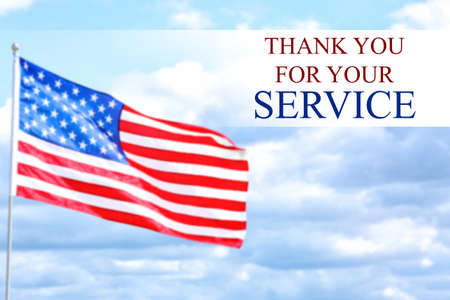 Text THANK YOU FOR YOUR SERVICE with USA flag against blue sky Stock Photo