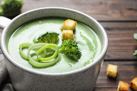 Fresh vegetable detox soup made of broccoli with croutons in dish on table, closeup