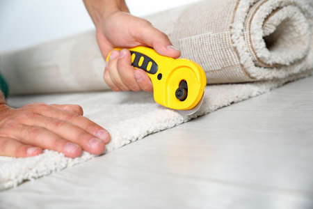 Man cutting new carpet flooring indoors, closeup. Space for text Stock Photo