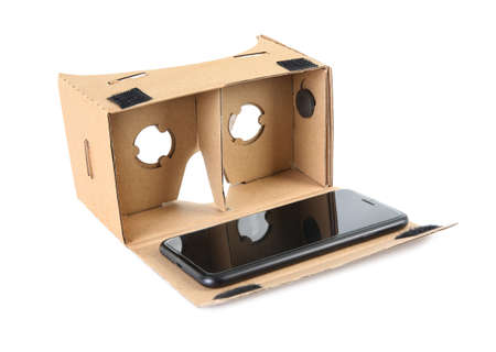 Cardboard virtual reality headset and smartphone on white background