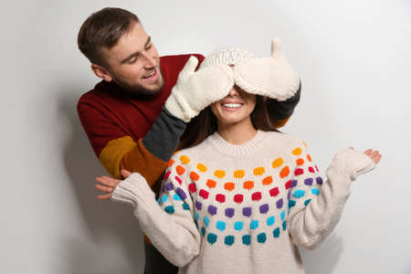 Young couple in warm sweaters on white background 스톡 콘텐츠