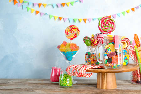 Composition with many different candies on table. Space for text