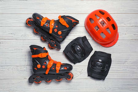 Flat lay composition with inline roller skates on wooden background