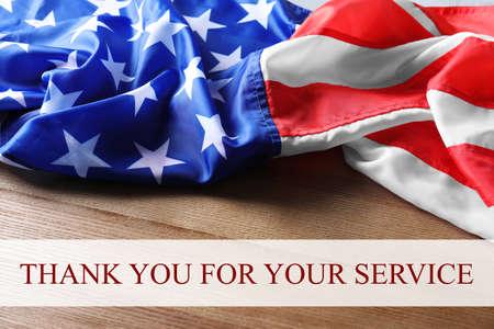 Texto GRACIAS POR SU SERVICIO y la bandera de Estados Unidos sobre fondo de madera