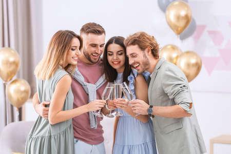 Glückliche Freunde mit Champagner in Gläsern zu Hause