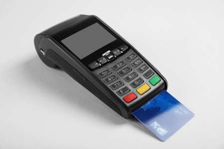 Modern payment terminal with credit card on grey background
