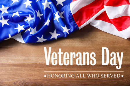 Text VETERANS DAY and USA flag on wooden background, top view. Honoring all who served Stock Photo
