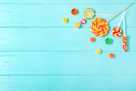 Flat lay composition with different candies and space for text on color wooden background Stock Photo