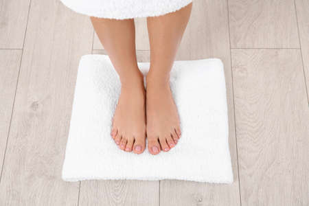 Woman with beautiful legs and feet standing on towel indoors, closeup. Spa treatment Standard-Bild