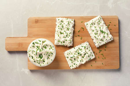 Tasty snack with cream cheese on gray table, flat lay
