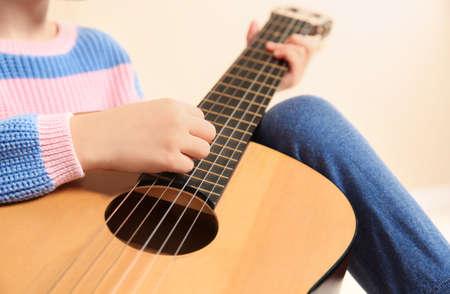 Little girl playing wooden guitar, closeup view 写真素材