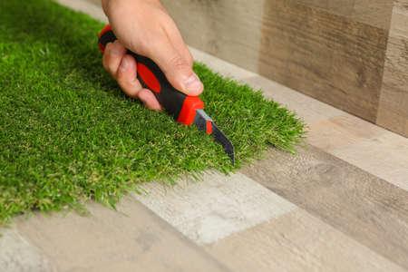 Man cutting artificial grass carpet indoors, closeup. Space for text