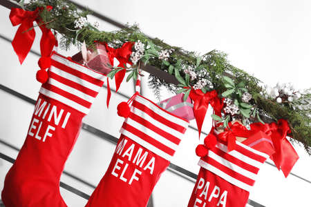 Red Christmas stockings with gift boxes hanging on stair railing, indoors. Festive interior