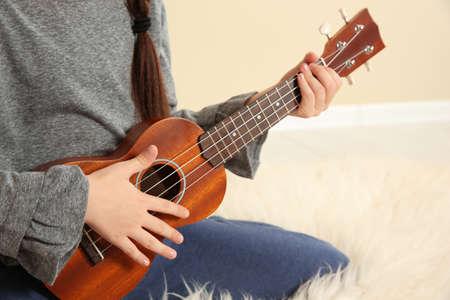 Little girl playing wooden guitar indoors, closeup