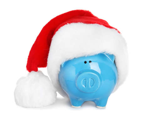 Cute piggy bank with Santa hat on white background Stock Photo