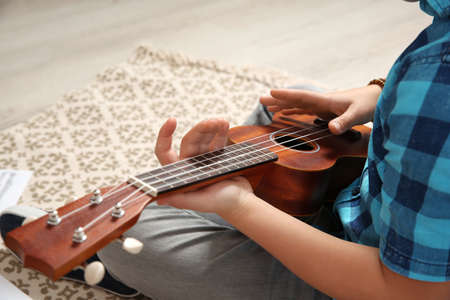 Little boy playing guitar on floor, closeup 写真素材