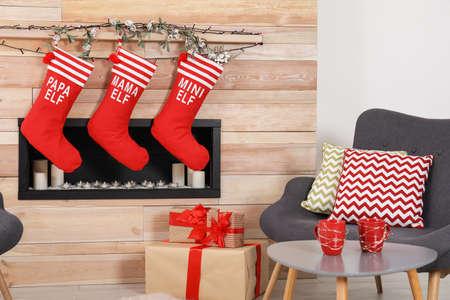 Weihnachtsinterieur mit Strümpfen und dekorativem Kamin