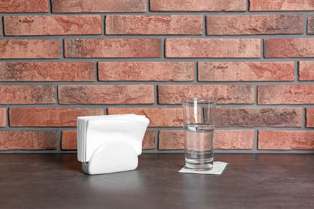 Napkin holder with paper serviettes and glass of water on table near brick wall