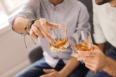 Friends toasting with glasses of whiskey indoors, closeup 版權商用圖片