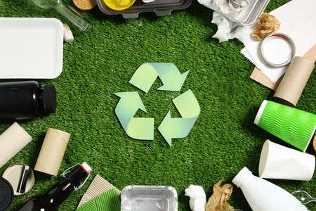 Simbolo del riciclaggio e diversi rifiuti su erba sintetica
