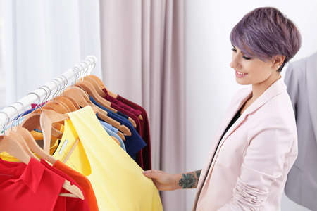 Beautiful young stylist choosing trendy clothes from rack in studio Stockfoto